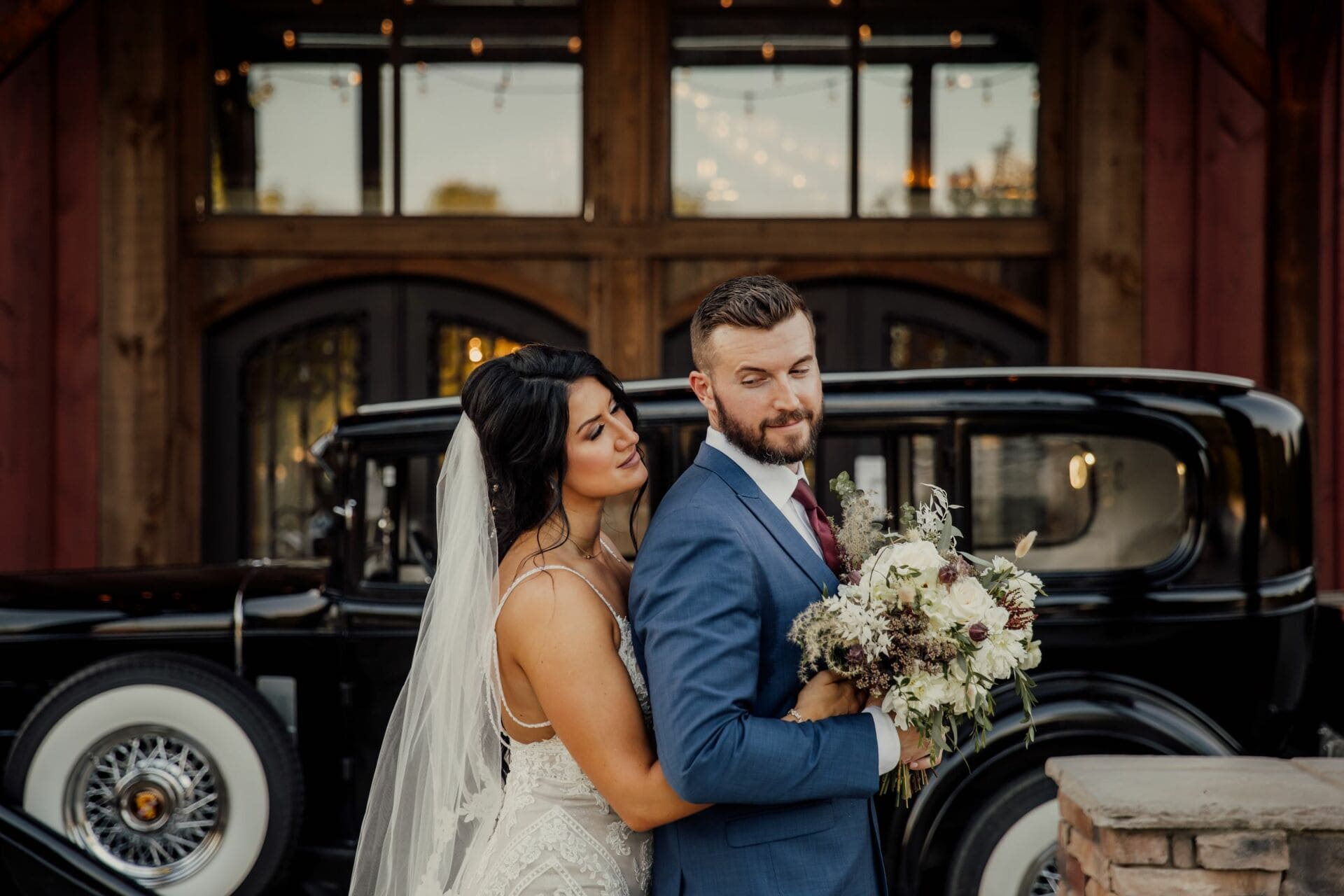 a couple pose in front of car at a Chattanooga wedding venue